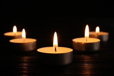 Burning candles on dark surface. Memory day