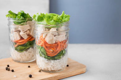 Healthy salad in glass jars on light table. Space for text