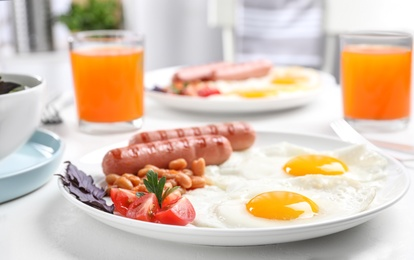 Delicious breakfast with fried eggs and sausages served on white table, closeup
