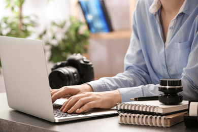 Journalist working with laptop at table, closeup