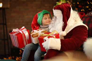Santa Claus and little boy with Christmas gifts indoors