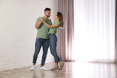 Lovely young couple dancing together at home