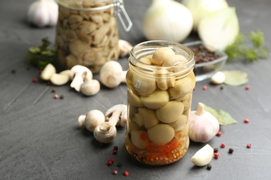 Glass jar of pickled mushrooms and ingredients on grey table. Space for text