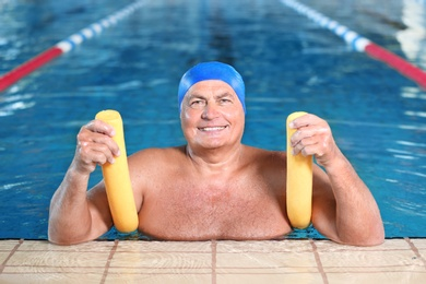 Sportive senior man with swimming noodle in indoor pool