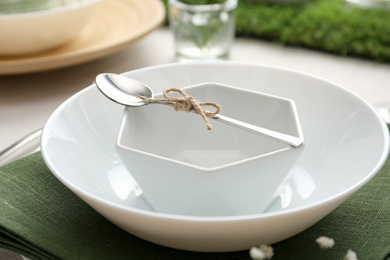 White dishes with spoon on table, closeup. Festive setting