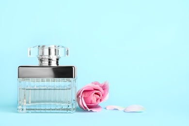 Bottle of perfume and beautiful rose on light blue background. Space for text