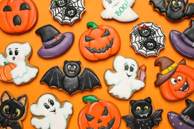 Different decorated gingerbread cookies on orange background, flat lay. Halloween celebration