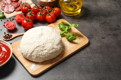 Dough and fresh ingredients for pepperoni pizza on grey table