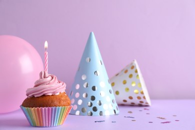 Delicious birthday cupcake with candle near party hats  and balloon on violet background, space for text