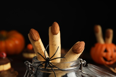 Delicious desserts decorated as monster fingers on dark background, closeup. Halloween treat