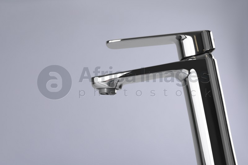 Single handle water tap on grey background. Space for text
