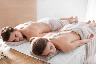 Romantic young couple receiving hot stone massage in spa salon