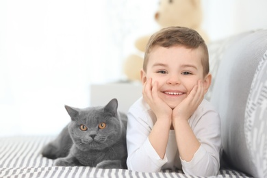 Cute little child with cat at home