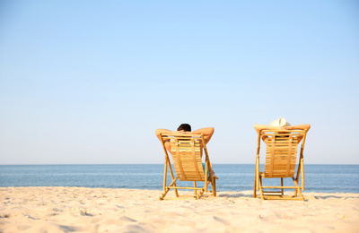 Couple resting on sunny beach at resort. Space for text