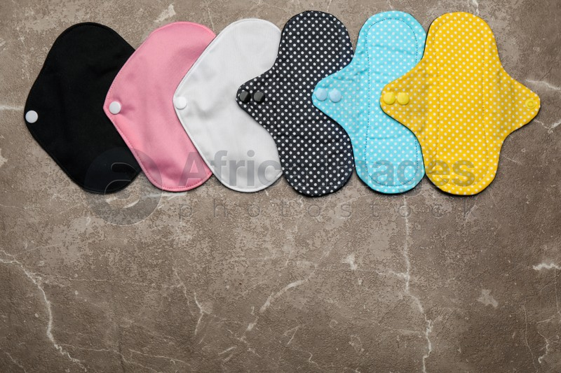 Many reusable cloth menstrual pads on brown table, flat lay. Space for text