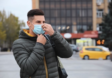 Man putting on medical face mask while walking outdoors. Personal protection during COVID-19 pandemic