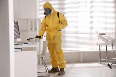 Man in protective suit sanitizing doctor's office. Medical disinfection