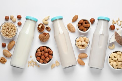 Vegan milk and different nuts on white background, flat lay