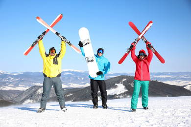 Friends with equipment at ski resort. Winter vacation