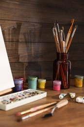 Easel with canvas and art supplies on wooden table