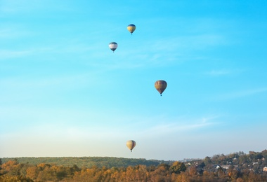 Colorful hot air balloons flying over countryside