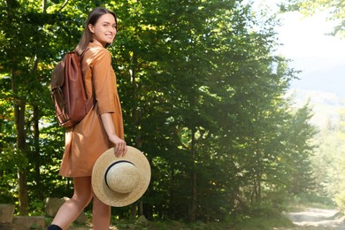 Happy woman with backpack and hat enjoying her walk in forest