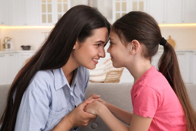 Happy mother and daughter touching foreheads at home. Single parenting