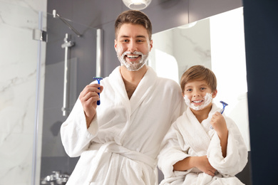Dad and son with shaving foam on faces holding razors in bathroom