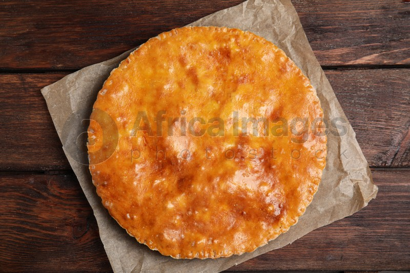 Delicious pie with meat on wooden table, top view