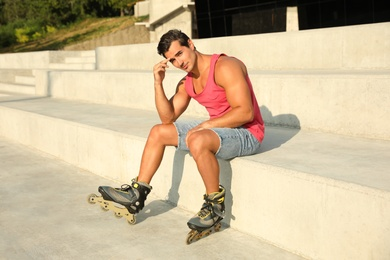 Handsome young man with inline roller skates sitting on stairs outdoors