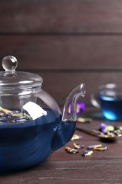 Organic blue Anchan in teapot on wooden table, space for text. Herbal tea