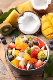 Delicious fresh fruit salad in bowl on wooden table