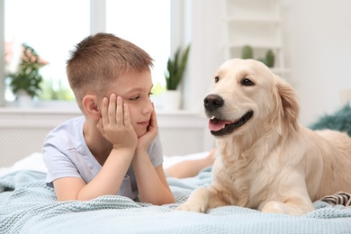 Cute little child with his pet on bed at home