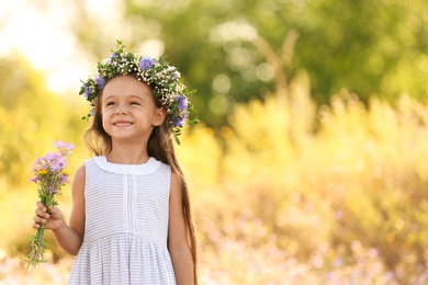 Cute little girl wearing beautiful wreath with bouquet of wildflowers outdoors, space for text. Child spending time in nature