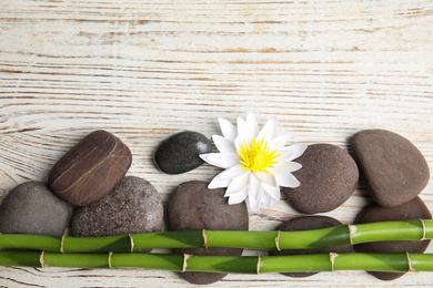 Stones, bamboo, lotus flower and space for text on white wooden background, flat lay. Zen lifestyle