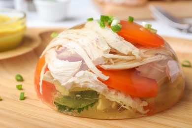 Delicious chicken aspic with vegetables on wooden plate, closeup