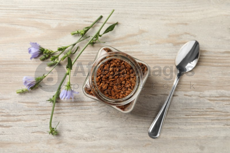 Jar of chicory granules, spoon and flowers on white wooden table, flat lay