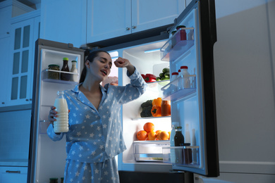 Young woman with bottle of milk near open refrigerator at night