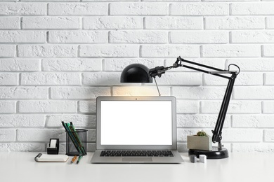 Modern workplace with laptop and lamp on table near brick wall. Space for design