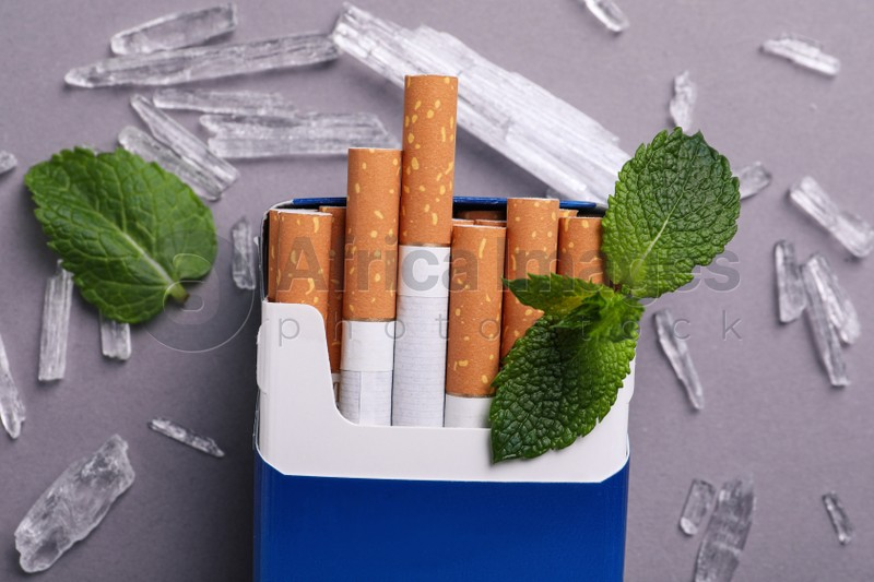 Pack of cigarettes, menthol crystals and mint leaves on grey background, flat lay