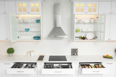 Open cabinets with different clean tableware and utensils in kitchen