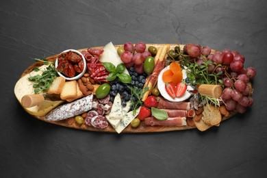 Set of different delicious appetizers served on black table, top view