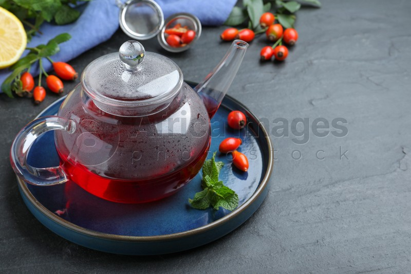 Teapot with aromatic rose hip tea, berries and mint on black table, space for text
