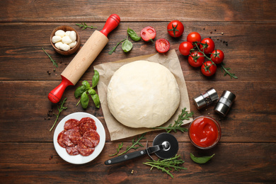 Flat lay composition with dough and fresh ingredients for pepperoni pizza on wooden table