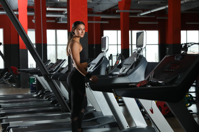 Young woman working out on treadmill in modern gym