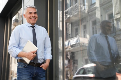 Portrait of handsome businessman with tablet in city