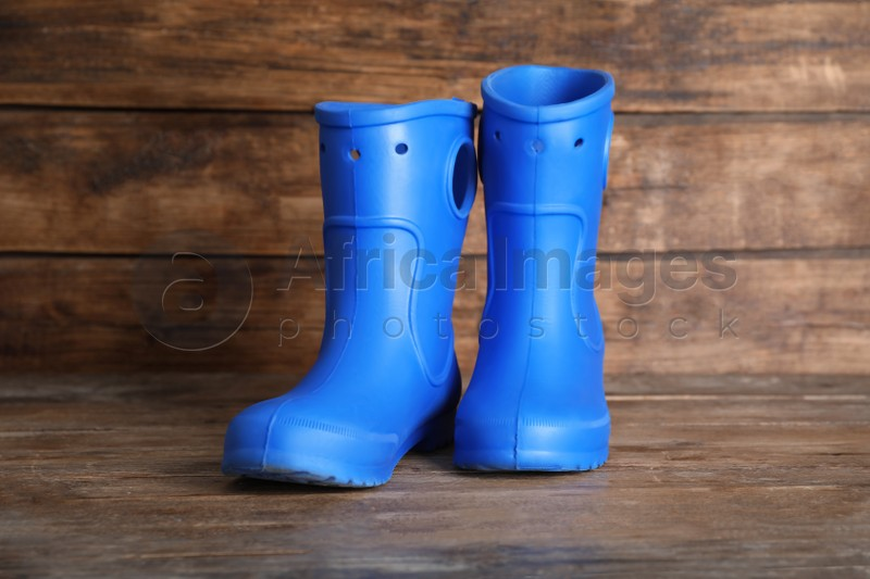 Bright blue rubber boots on wooden surface
