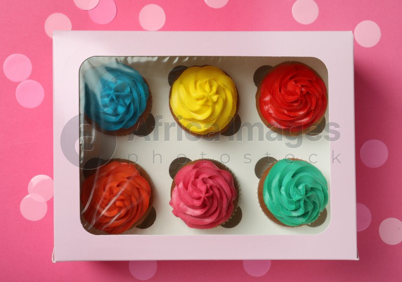 Box with different cupcakes and confetti on pink background, flat lay