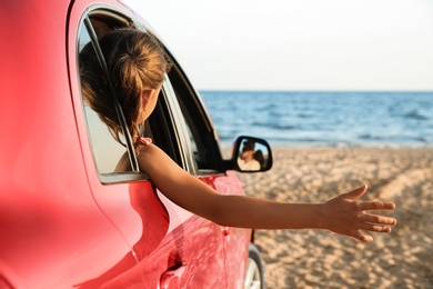 Little girl leaning out of car window on beach. Summer trip