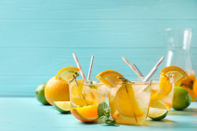 Delicious refreshing drink with orange and lime slices on light blue wooden table